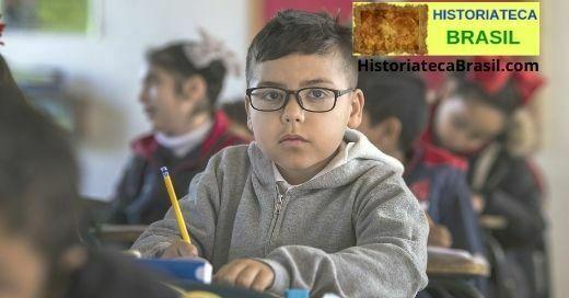 criança de óculos escrevendo na escola